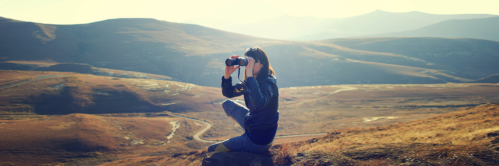 A woman sitting on a hill with binoculars