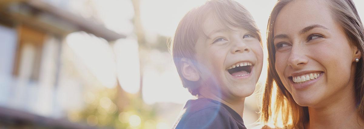 Joven con un niño riendo