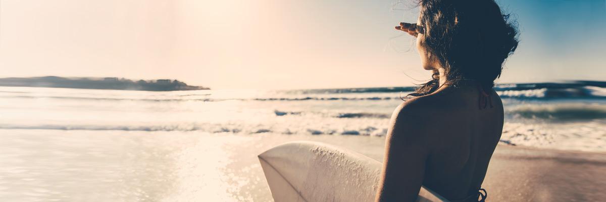 Jeune femme avec planche de surf
