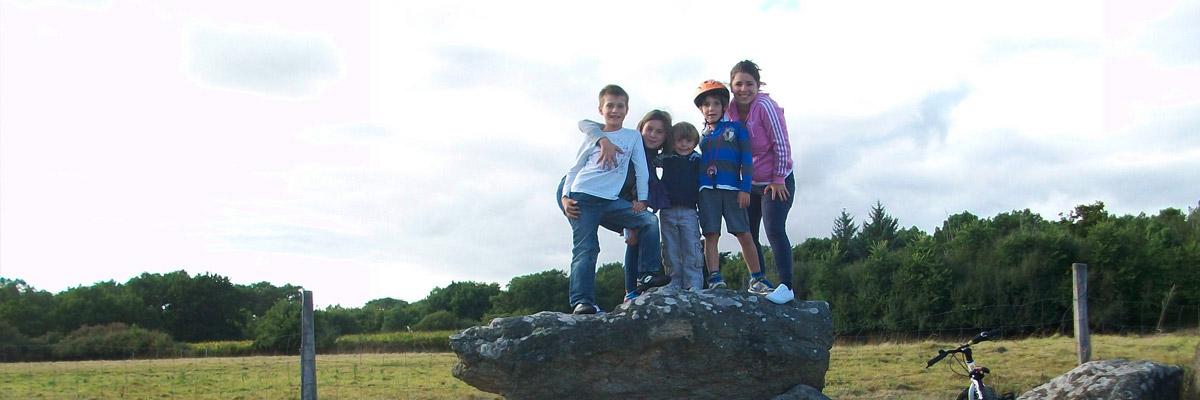 Marta con sus hijos invitados en una piedra.