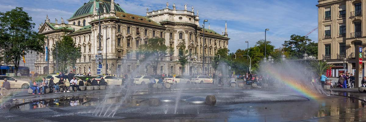 The fountain and the sunlight create a little rainbow in the city centre of Munich