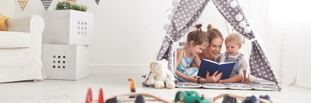 Una au pair con sus niños de acogida leyendo un libro en una tienda de campaña