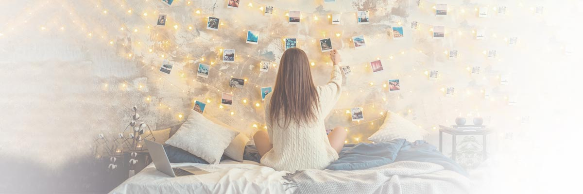 Girl sitting on her bed in her room, watching photos