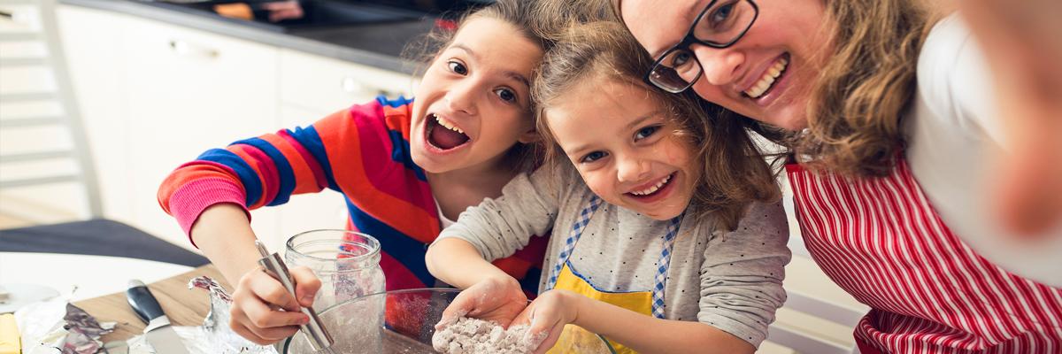 Due bambini che cucinano con una ragazza alla pari