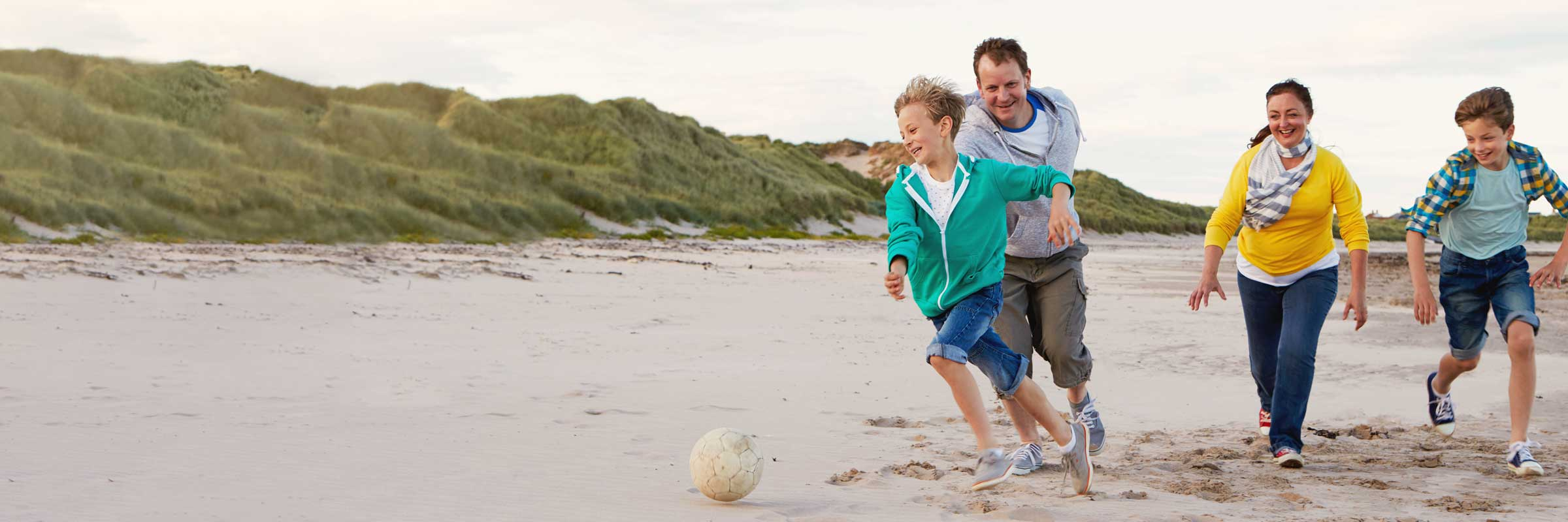 A family plays football on the beach.