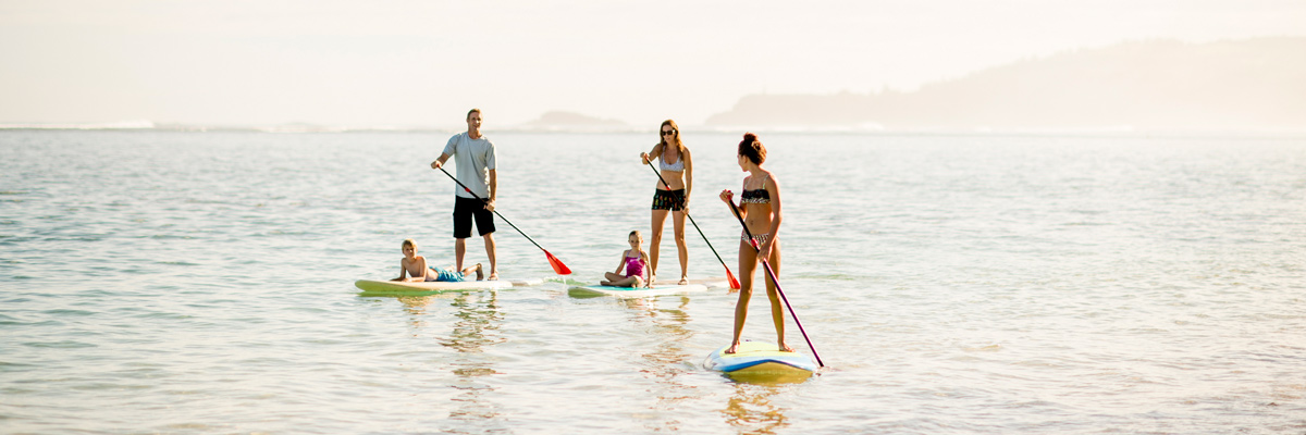 The host family and their au pair enjoying time together while doing stand up paddling