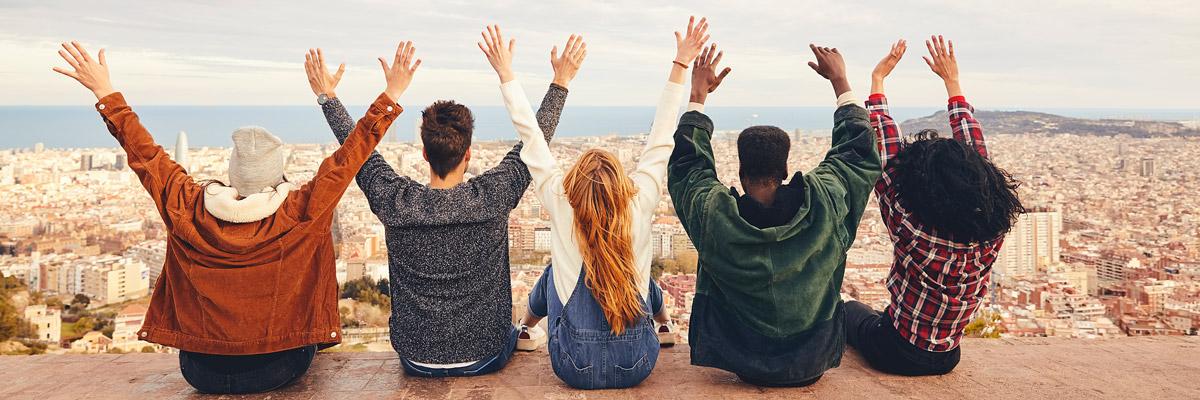 Grupo de jóvenes levantando las manos