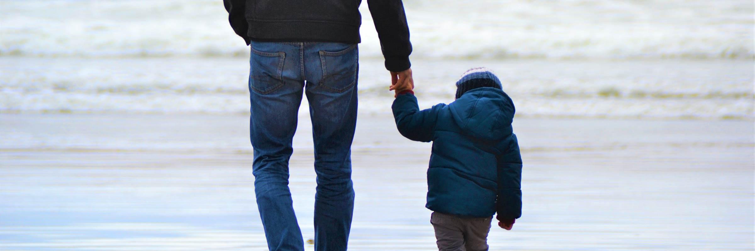 Un homme et un enfant se tiennent la main à la plage