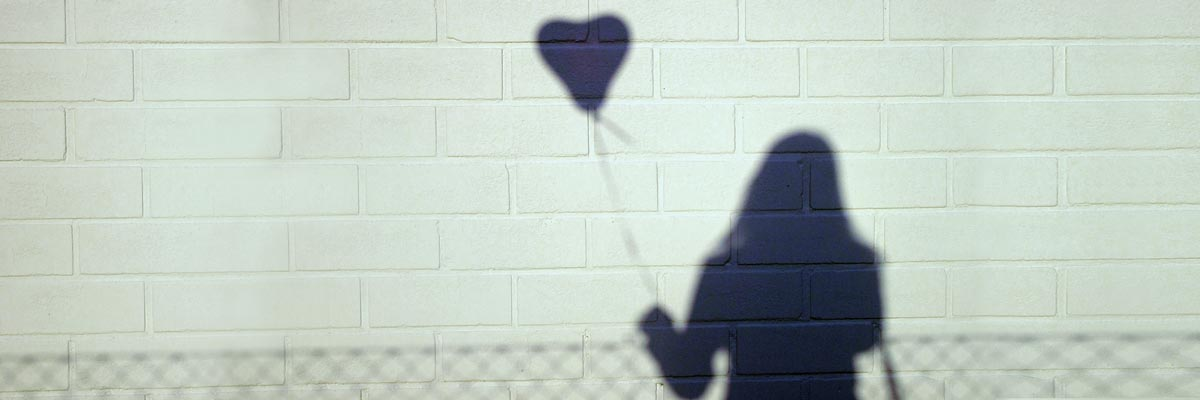 shaddow of a girl with a heart ballon in her hand