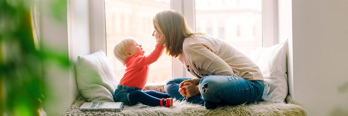 Baby und Au Pair beim Spielen am Fenster