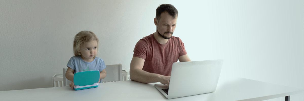Vater und Tochter sitzen vor einem Laptop