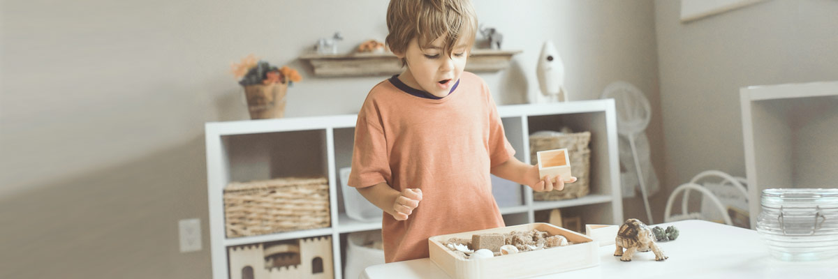 Enfant jouant avec des jouets naturels.