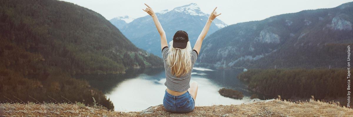 Mujer frente a un lago y montañas