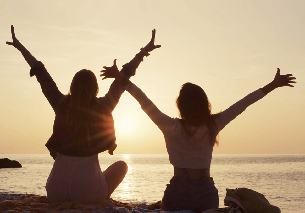 Two girls looking out to sea with arms outstretched as the sun goes down