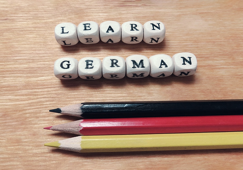 "Dices with letters ""Learn German"" beside 3 crayons in black, red and yellow"