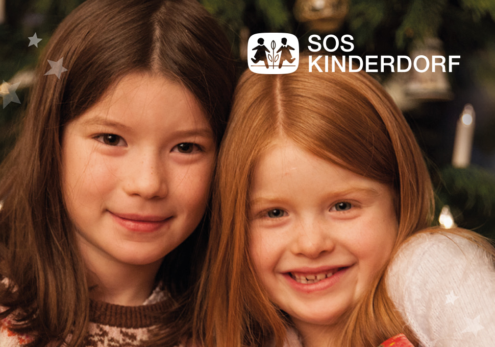 Two girls look at the camera with the SOS Children's Village logo in the background