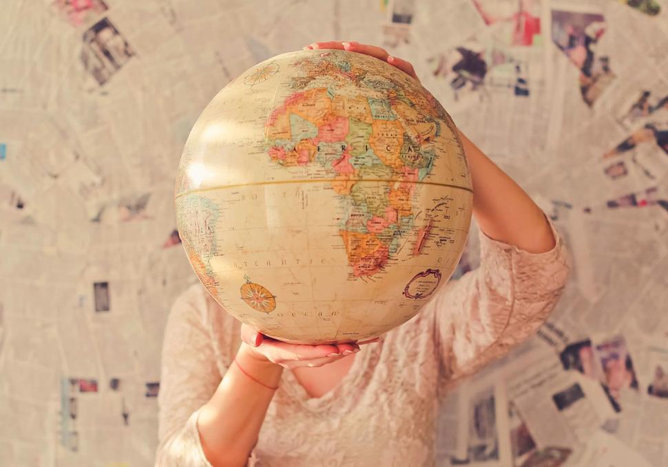 Junge Frau hält Weltkugel hoch