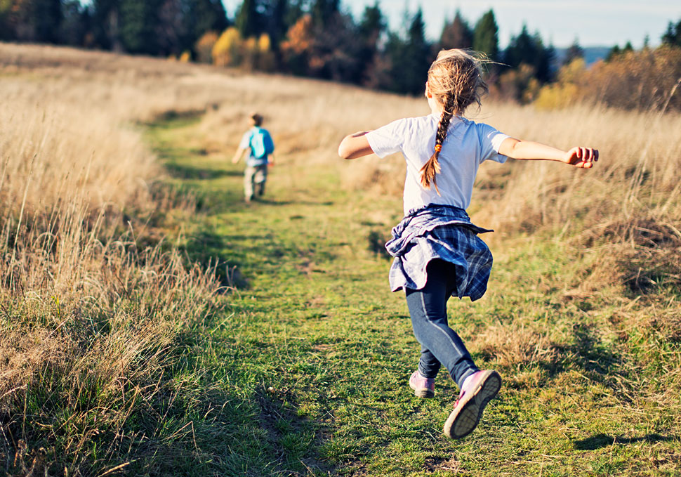 Young children running across a meadow