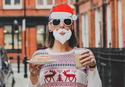 Une jeune dame portant un bonnet père Noël et une arbe