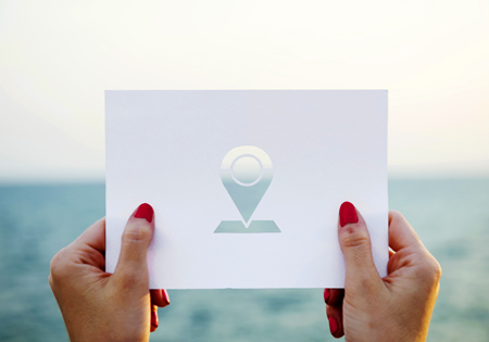 Woman's hands holding card with location icon