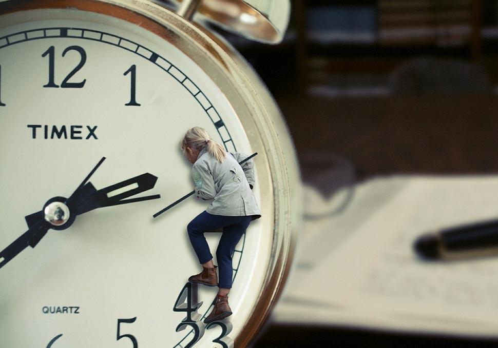 Blondes kleines Kind klettert auf den Zahlen und Zeigern der Uhr