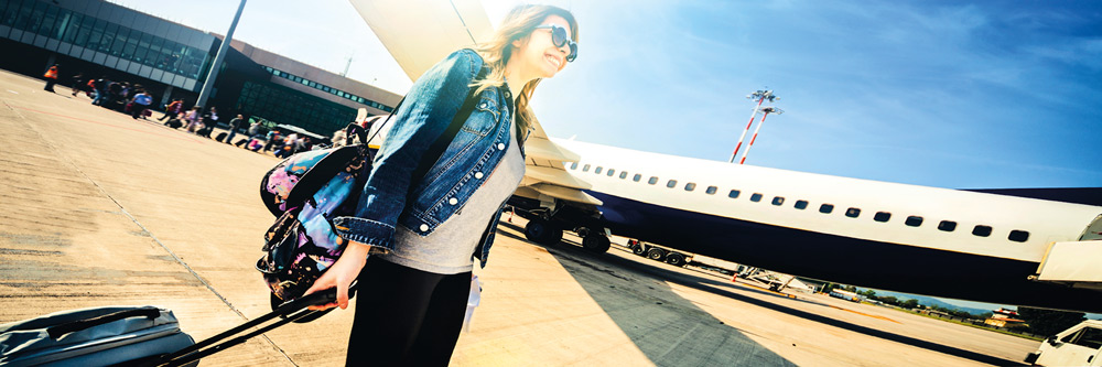 Chica joven con la maleta en el aeropuerto