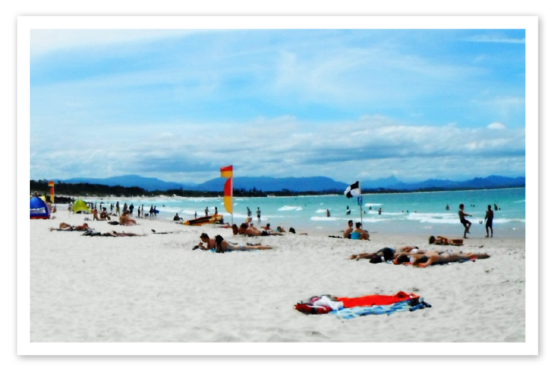 People relaxing on a beach at Byron Bay