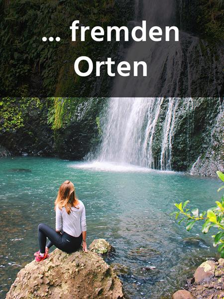 Mädchen sitzt vor einem Wasserfall
