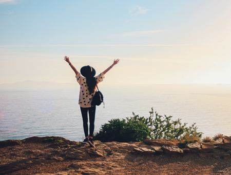 Junge Frau schaut über das Meer in Richtung Horizont