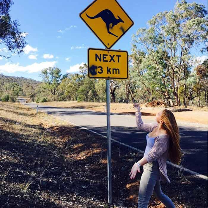Nina debajo de una señal de tránsito australiana
