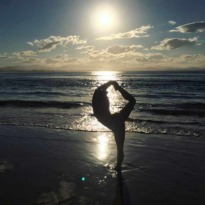 Nina on the beach doing yoga
