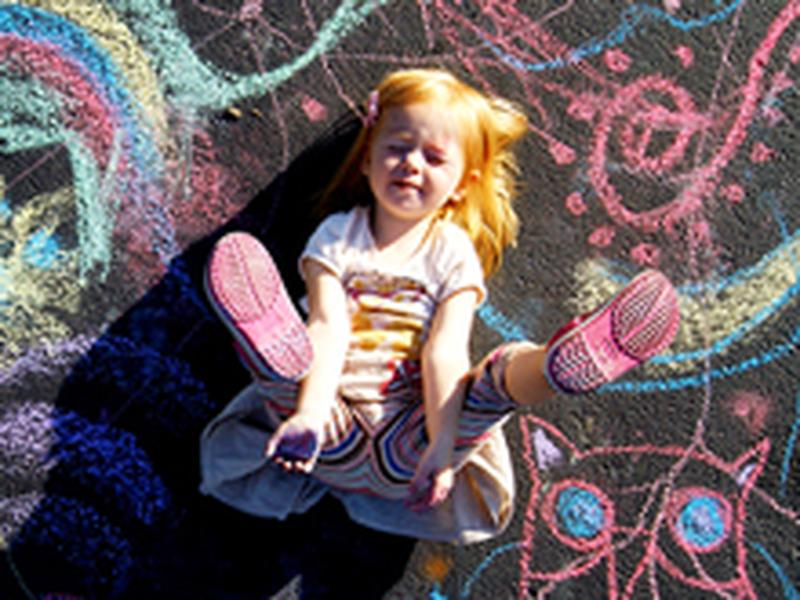 A little girl plays with chalk on the street
