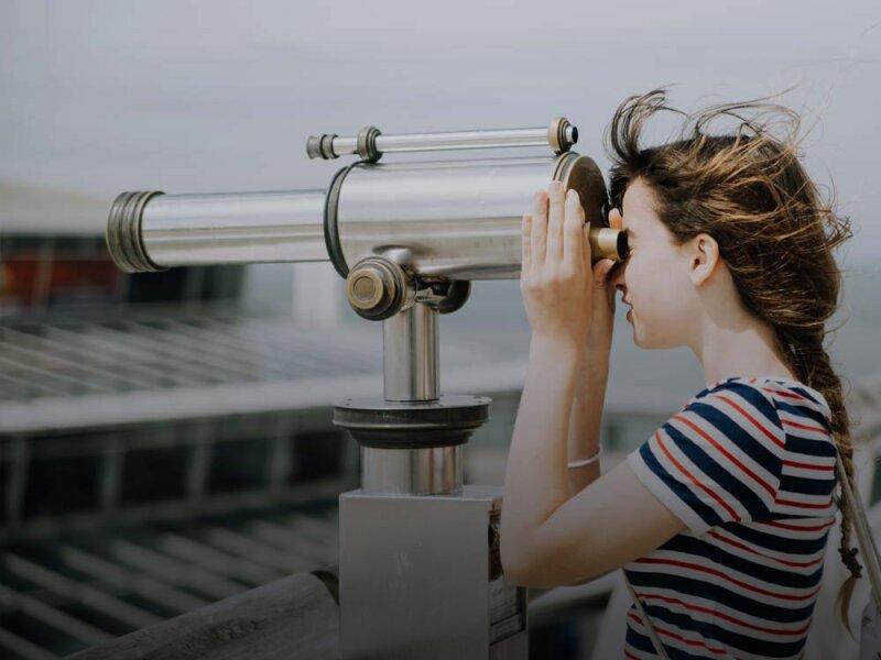 Een meisje kijkt door een telescoop op het strand