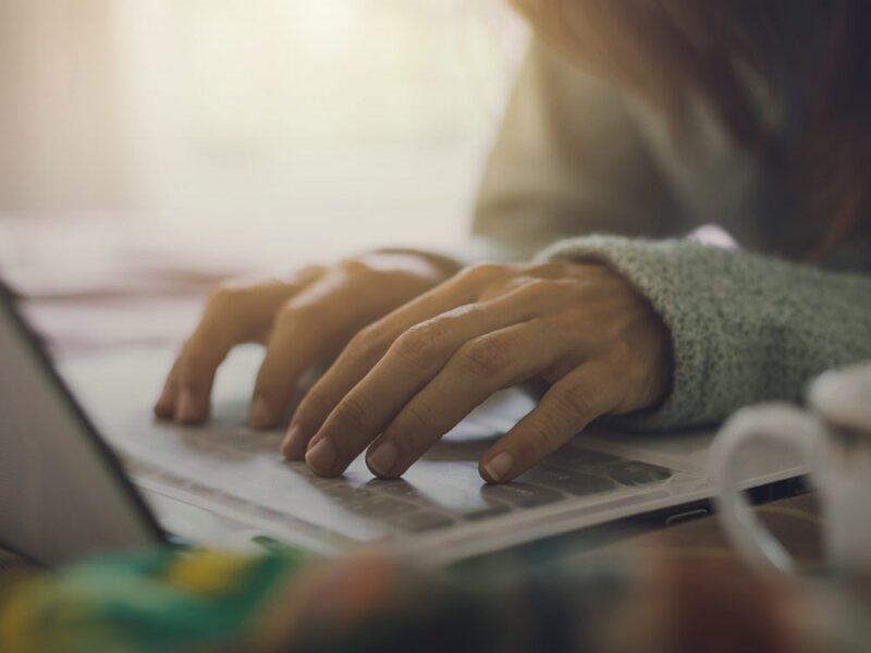 Twee handen typen op een computertoetsenbord