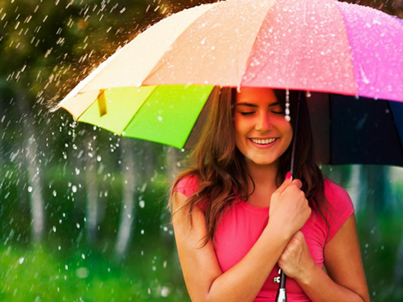 Ragazza con un ombrello sotto la pioggia