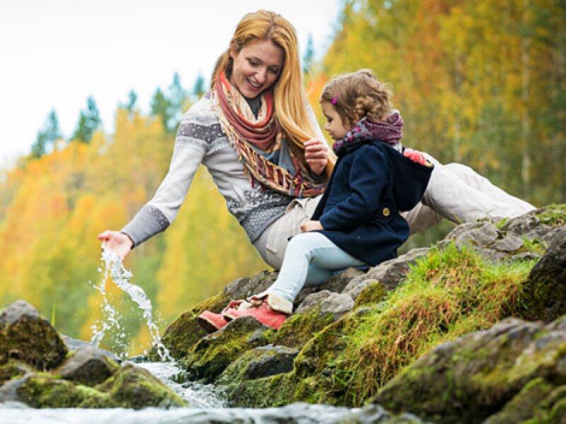 Jonge vrouw speelt met een kind naast een beek