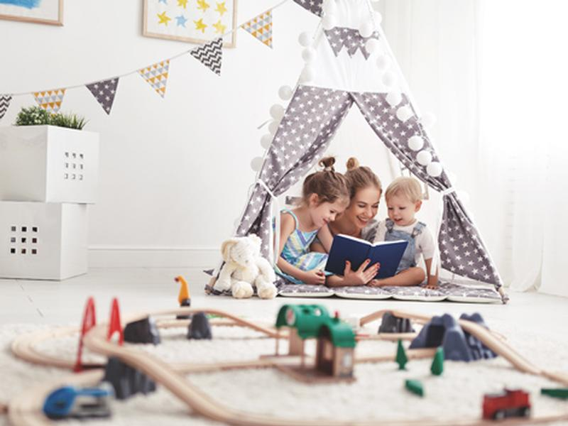 Des enfants avec un jeune au pair sous une tente