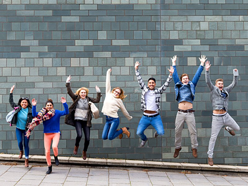 Happy young people jumping upwards