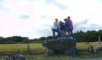 Marta en una roca en un paseo en bicicleta con sus hijos