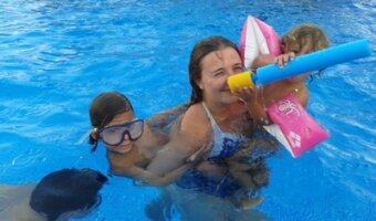 Marta con sus hijos invitados en la piscina.