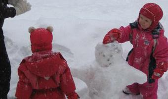 Tiinas's children are building a snowman with their Spanish au pair.