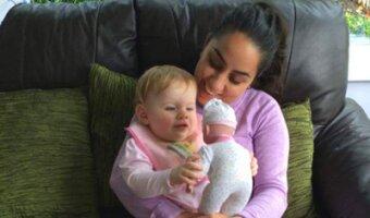 Gastkind sitzt auf Amandas Schoß und spielt mit einer Puppe