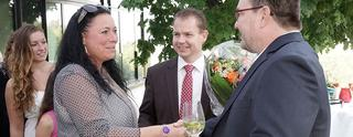 Some guests with a bouquet of flowers greet Uwe Regenbogen