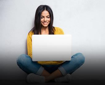 Young woman sitting cross-legged with a laptop on her lap